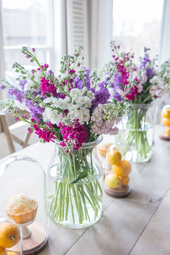 bold floral arrangements are always a good idea of a spring centerpiece, lemons in cloches add to the look