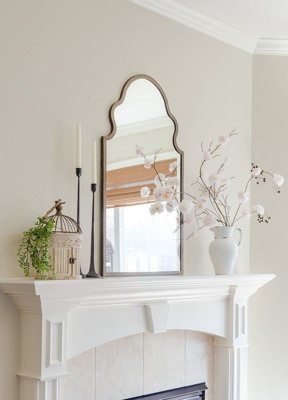 chic spring mantel decor with faux blooms in a jug, a decorative cage with greenery, a mirror and a couple of candles