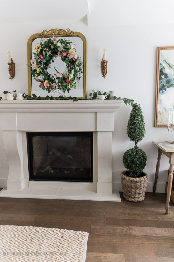 classic spring mantel decor with a mirror and a bright faux bloom wreath on it, a greenery runner, mini jugs and green topiaries in a basket