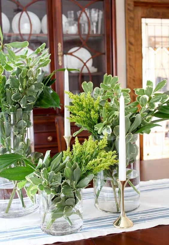 glass vases with greenery and some mimosa flowers compose a cluster spring centerpiece to enjoy