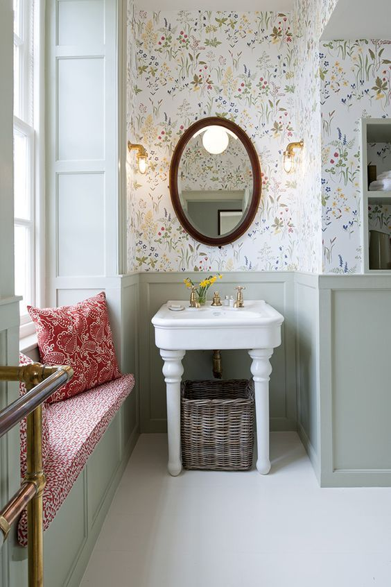 lovely colorful floral wallpaper adds a touch of color to this neutral farmhouse bathroom and a seat adss to the space, too