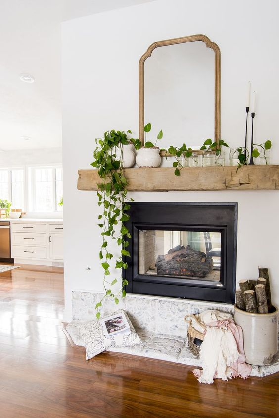 simple and chic spring mantel decor with potted greenery, candles and jars with leaves, a basket with blankets and firewood