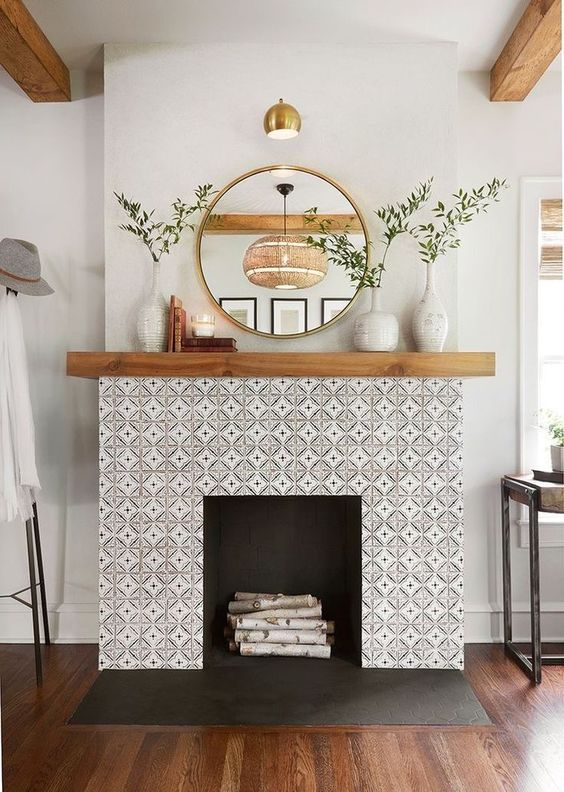 simple and elegant modern spring mantel decor with greenery in matching vases, candles, stacked books and a round mirror