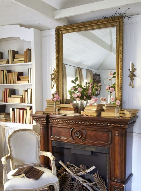 vintage spring mantel decor with stacks of vintage books, a gold framed mirror, pink blooms in vases and oversized pinecones in a bucket