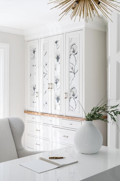 white built-in office cabinets boast doors accented with floral wallpaper and brass pulls look amazing