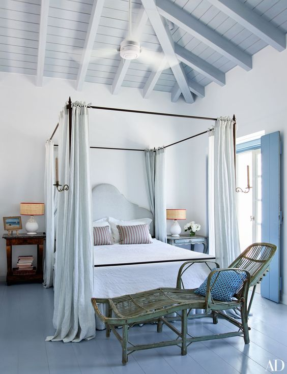 a beautiful coastal bedroom with a canopy bed, a rattan lounger at its foot, neutral bedding, mismatching nightstands