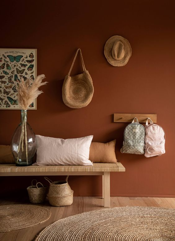 02 a boho entryway with a terracotta wall, a woven bench and a rack, some baskets and pampas grass in a large bottle