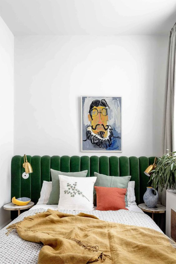 a green channel tufted headboard is a stylish art deco idea and gold sconces will make reading more comfortable