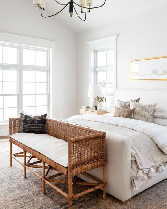 a beautiful neutral bedroom with a creamy upholstered bed, a rattan bench at the foor, a cool artwork over the bed