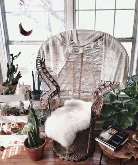 a peacock chair finished with tassel blankets and a white faux fur piece is a perfect boho piece to rock