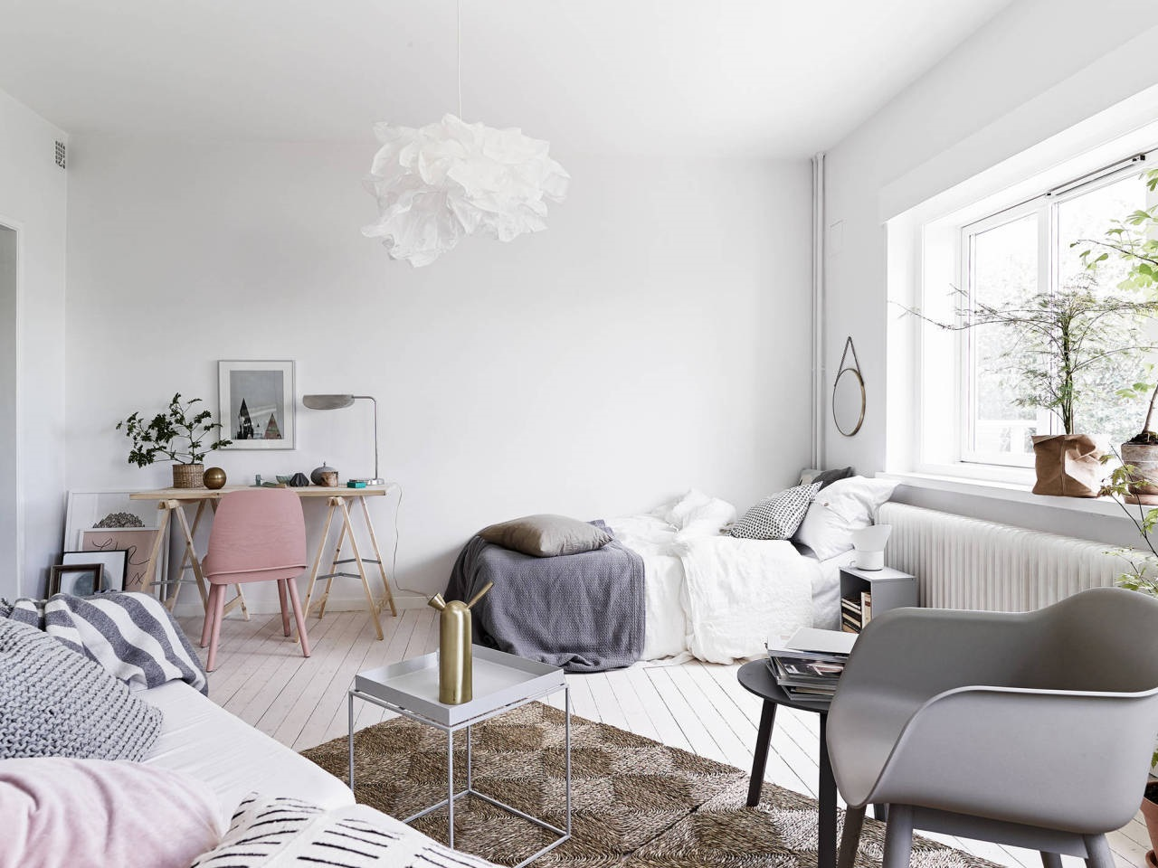an airy Scandinavian studio apartment done in neutrals and with pastels and some prints for an airy look
