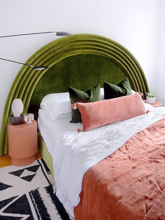 a beautiful curvy velvet headboard inspired by vintage and art deco pieces, some green pillows and coral bedding