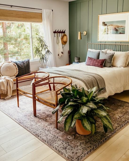 a boho chic bedroom with a green accent wall, a metal bed and matching sconces plus chic mid-century mdoern chairs at the foot