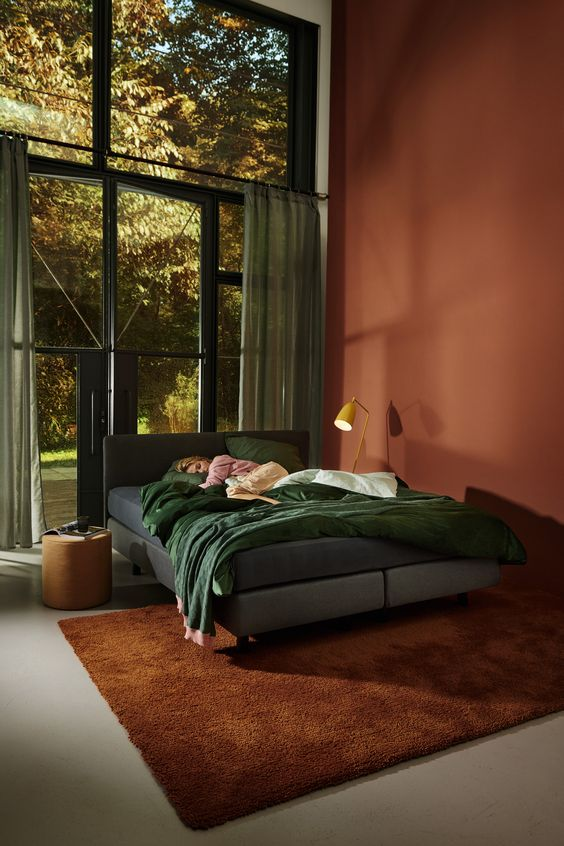 a bold bedroom with a terracotta wall, a grey upholstered bed, emerald bedding, a floor lamp and a round leather stool