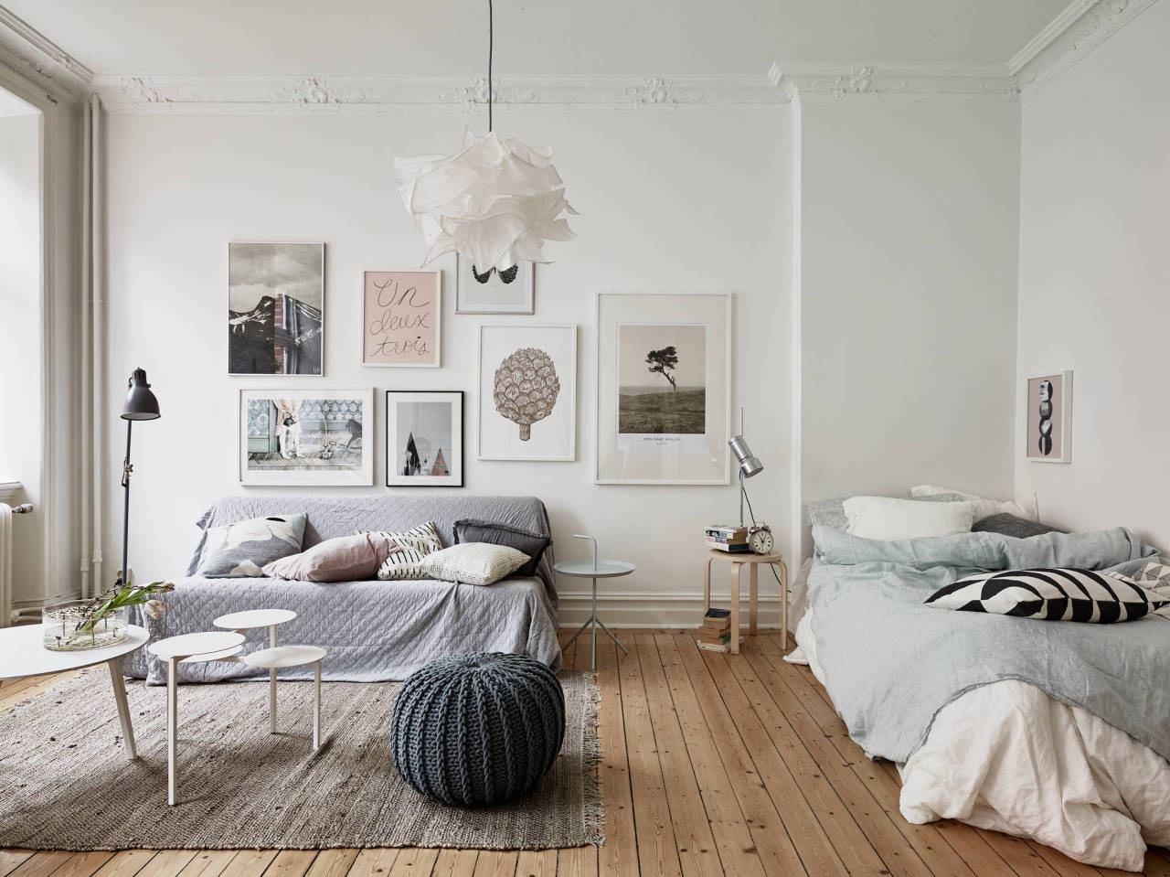 an airy Scandinavian studio apartment with touches of pastels, a lovely gallery wall and cool lamps