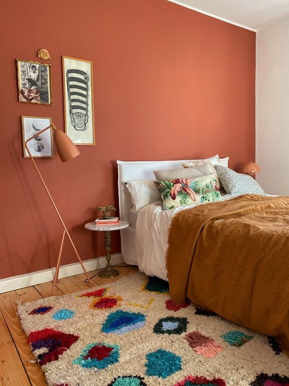 06 a bright bedroom with a terracotta accent wall, a white bed with eclectic bedding, a gallery wall and rust-colored lamps