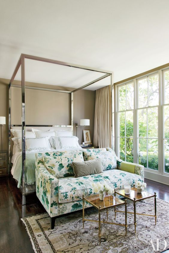 a chic bedroom with a taupe accent wall, a shiny metal canopy bed, a floral loveseat at its foot and cool side tables