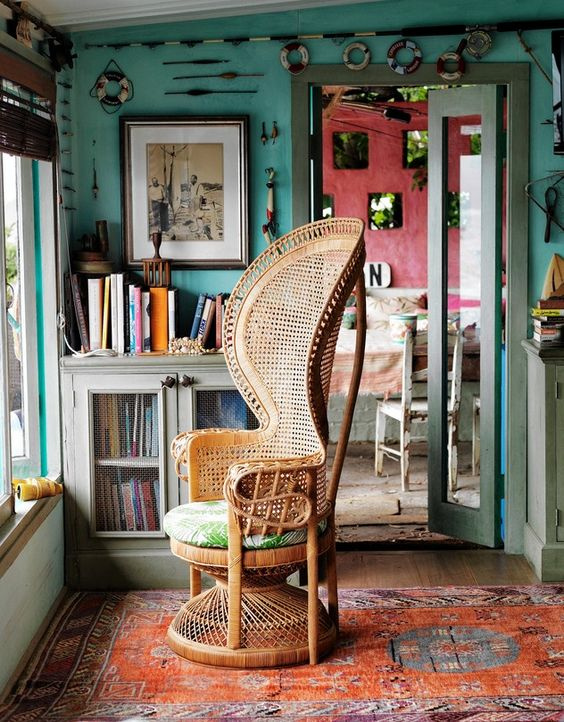 a cool and chic peacock chair with tropical print upholstery for completing a cozy boho reading nook