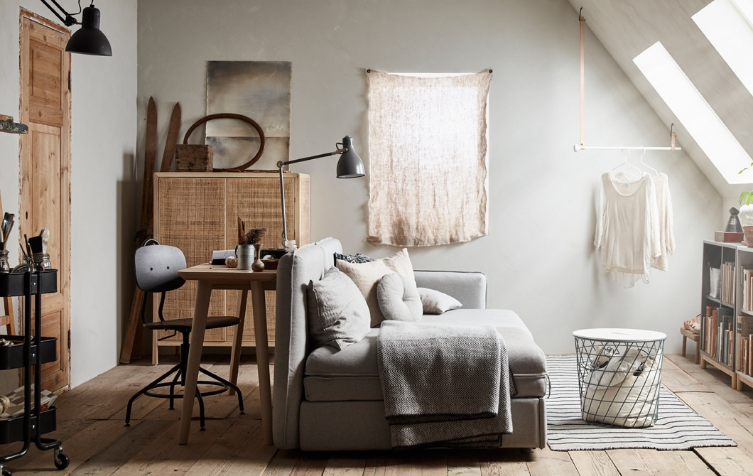 a small neutral studio apartment done with blonde wood furniture, neutral upholstery, retro lamps and an attic closet