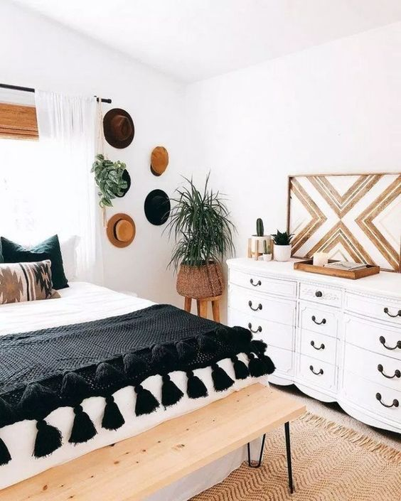 a chic boho bedroom with a bed, a hairpin leg bench at the foot, a refined dresser and tribal touches here and there