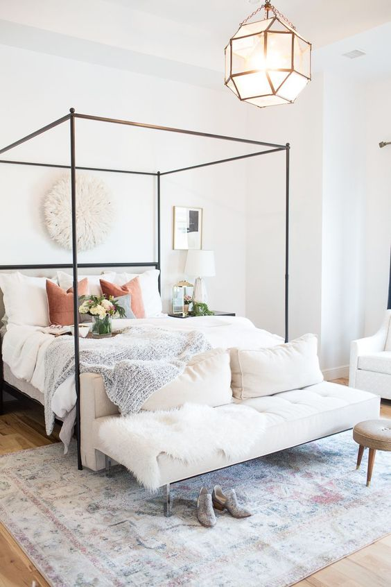 a chic modern bedroom in neutrals, with a metal canopy bed, a lovely upholstered bench at the foot, a faceted lamp