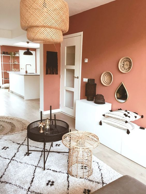 08 a cozy foyer with a terracotta accent wall, simple cabinets, round tables, a woven lamp and a small gallery wall