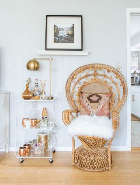 a peacock chair with a boho pillow and a whiet faux fur cushion is a lovely boho inspired idea for your home