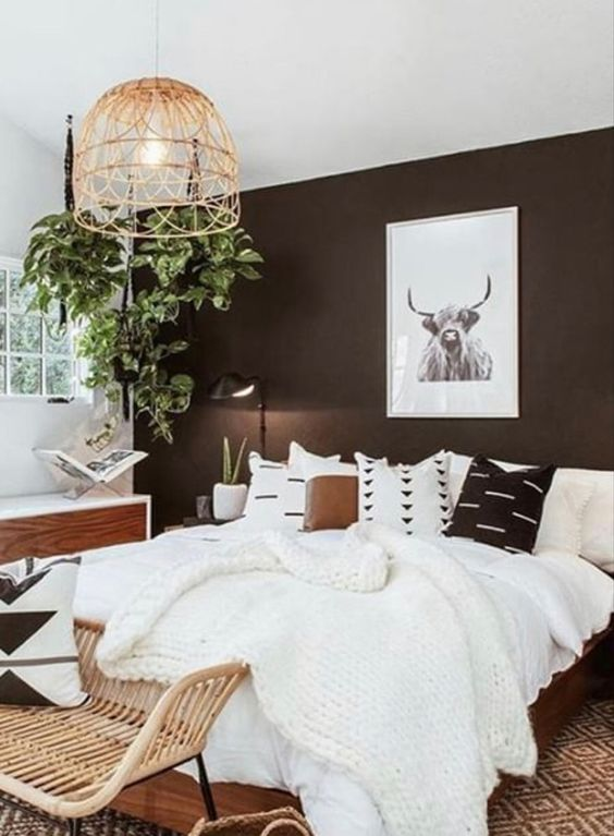 a cool monochromatic modern bedroom with a black accent wall, black and white graphic bedding and a rattan chair at the foot of the bed