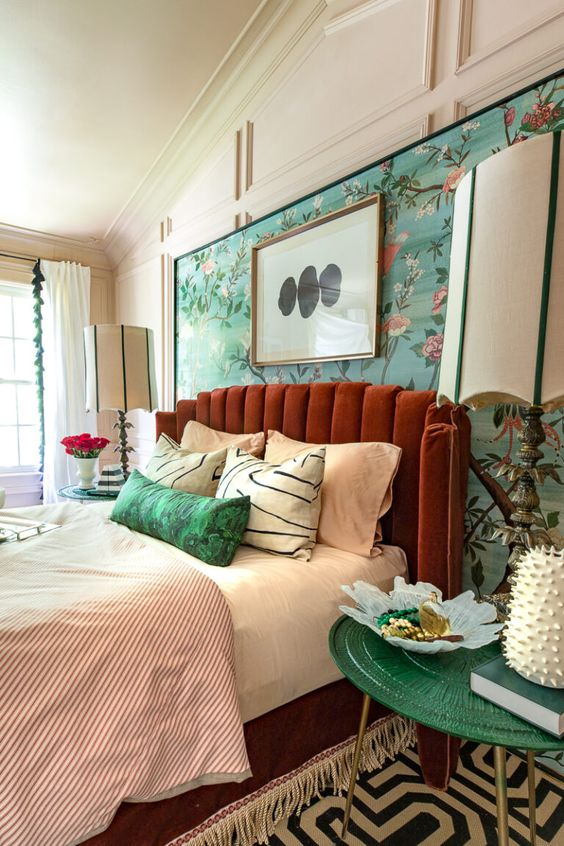 a gorgeous maximalist bedroom with a rust-colored bed with a tufted headboard in front of a floral wall