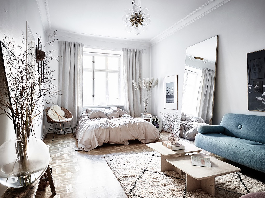an airy and chic Nordic studio apartment with a blue sofa, some grass arrangements and a large floor mirror