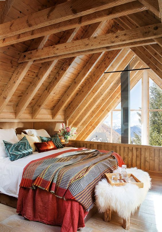 a cozy attic cabin bedroom with a glazed wall, a wooden bench with boho bedding and a wooden and faux fur bench at the foot