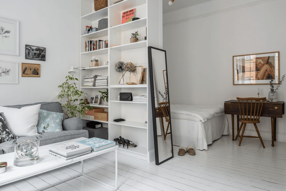 a high IKEA Billy bookshelf separates a small and cozy bedroom nook from the rest of the space