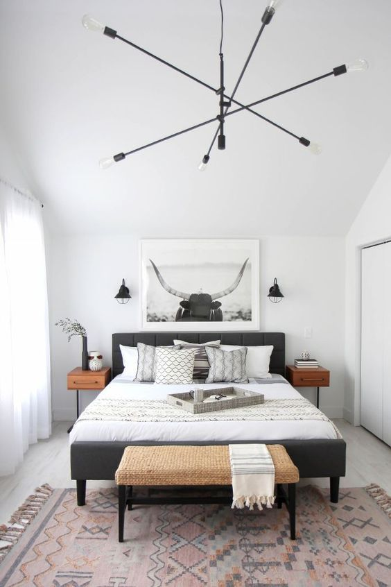 a gorgeous modern bedroom with a grey bed, a woven bench, a lovely chandelier, a monochromatic artwork over the bed