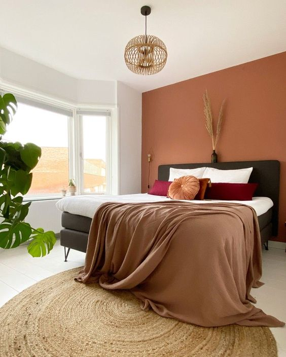11 a lovely bedroom with a boho feel, a terracotta accent wall, a black bed, bold bedding, a wooden pendant lamp and some plants