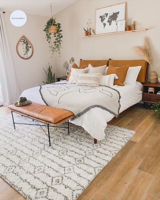 a lovely boho bedroom with a pretty and comfy bed, a leather bench at the foot, a hanging shelf and some greenery