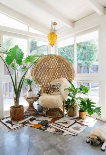 a stylish boho nook with a peacock chair, pillows and white fur, potted plants and layered rugs is super cool