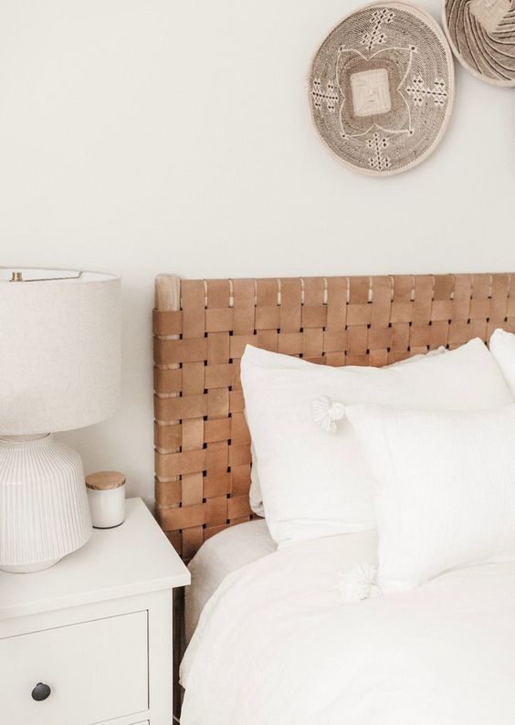 a neutral boho bedroom with decorative baskets, a bed with a woven leather headboard and neutral furniture