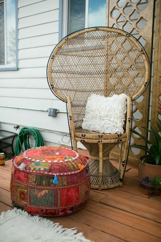 place a peacock chair and a bright boho ottoman outside to make your outdoor space boho and welcoming