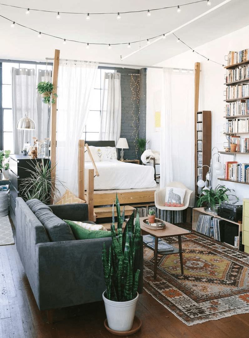 a boho studio apartment separated with light curtains and raised above the ground to give some under the bed storage space