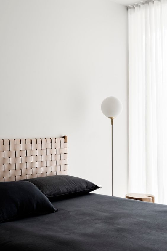 a minimalist bedroom with a woven ehadboard that adds interest to the sleek space and contrasts black bedding