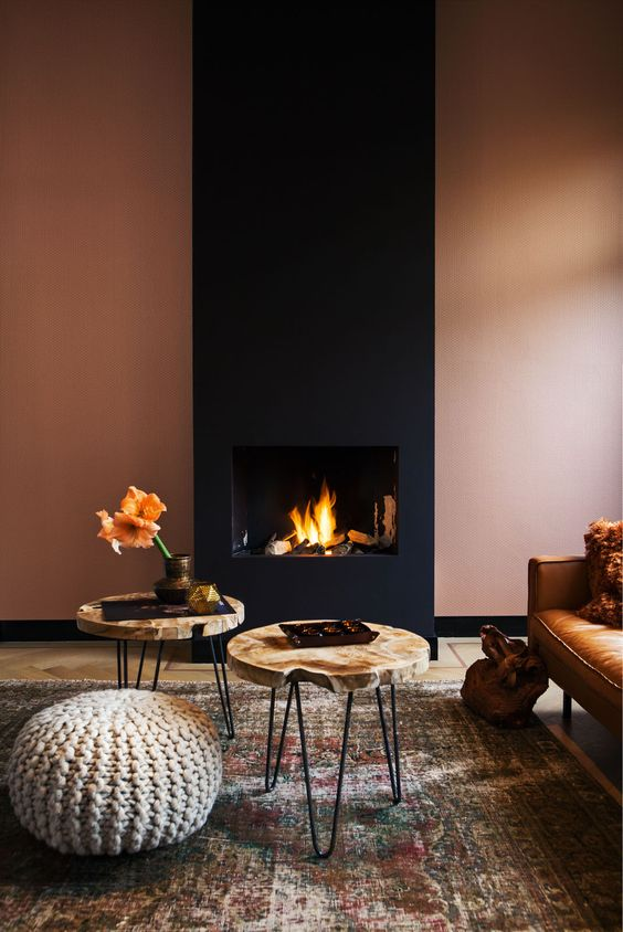 15 a refined modern living room with a rust-colored wall and a black fireplace, a leather sofa, wood slice tables and a knit ottoman