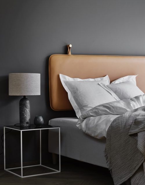 a minimalist bedroom with a moody color palette and a brown leather suspended headboard is a pretty idea