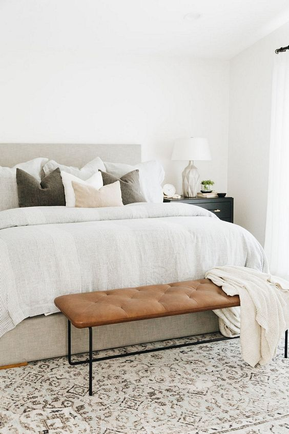 a neutral farmhouse bedroom with a grey upholstered bed, a leather bench, neutral layered bedding and a cool table lamp