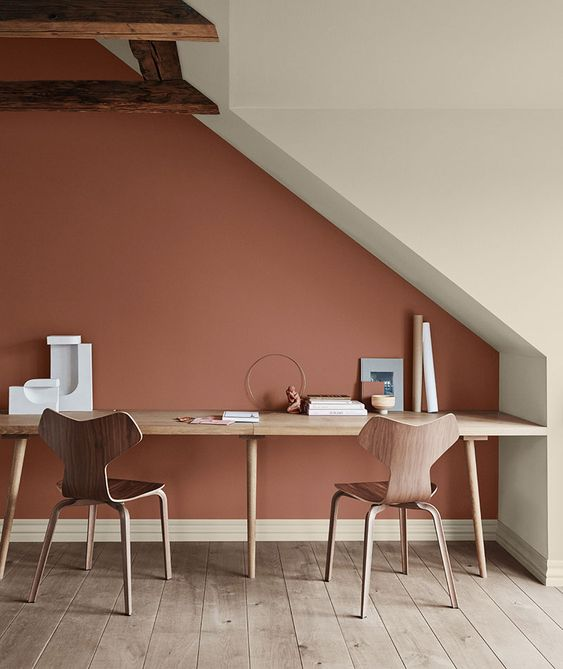 16 an attic shared work space with a shared desk, plywood chairs and a bold terracotta accent wall plus wooden beams