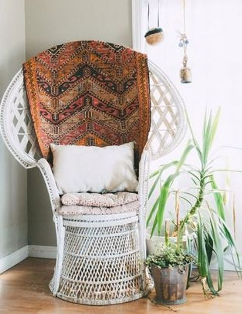 a chic white peacock chair with cushions, a pillow and a boho blanket is beautiful and cool idea for a boho space