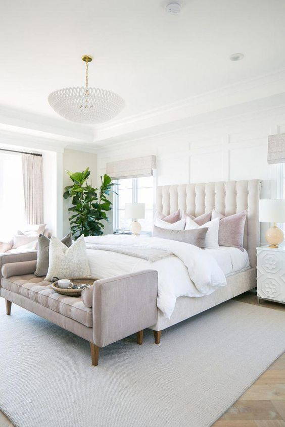 a neutral glam bedroom with a farmhouse touch, a creamy upholstered bed, a grey upholstered bench and a chic chandelier