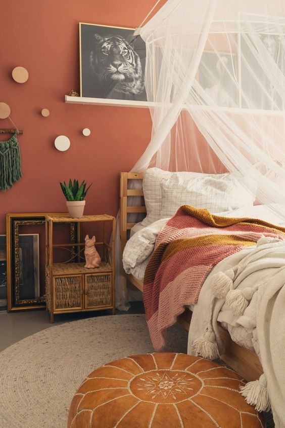 17 an eclectic bedroom with a terracotta accent wall, wooden and rattan furniture, neutral and bright bedding, a canopy and a gallery wall on a ledge