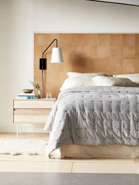 an extended leather headboard liek this one will add a warm touch of color and texture to the space