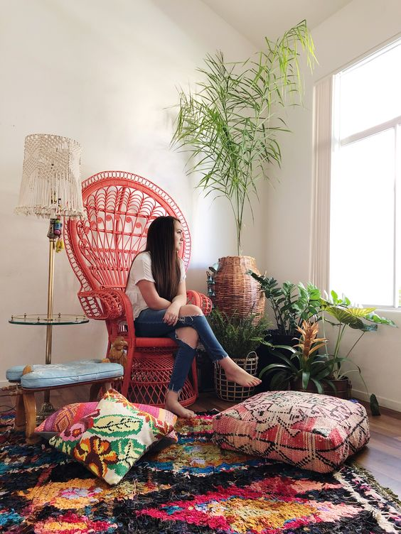 a coral pink peacock chair, bright ottomans and pillows, a colorful rug and potted plants for a bright boho space