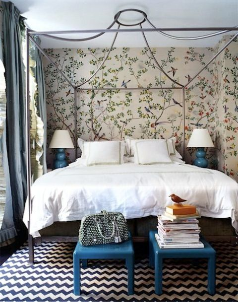 a pretty bedroom with floral wallpaper walls, a canopy bed, neutral bedding, bright blue stools and matching lamps